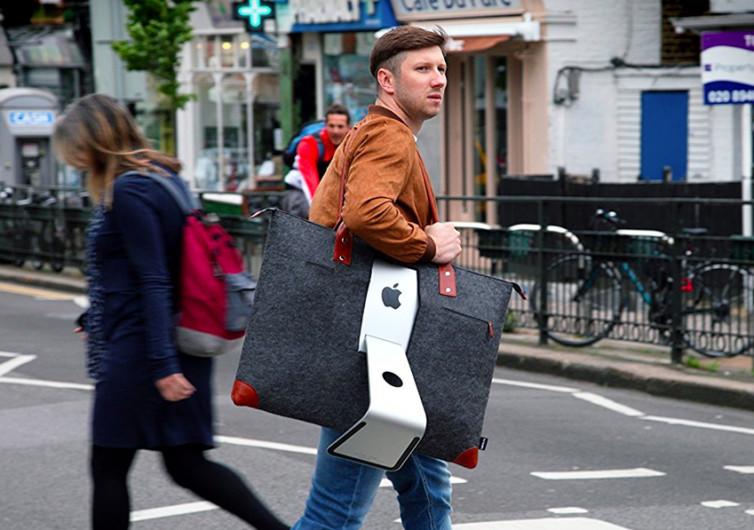 un homme transporte son mac apple dans un sac de transport adapté