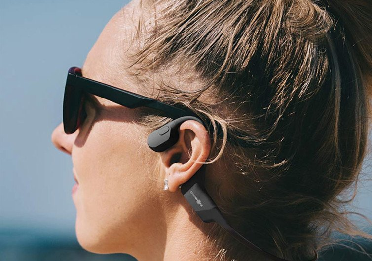 la tête d'une femme qui porte sur les oreilles un casque de musique AfterShokz Aeropex