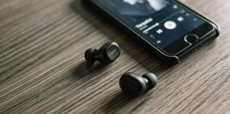 des ecouteurs sans fils posés sur une table à côté d'un smartphone