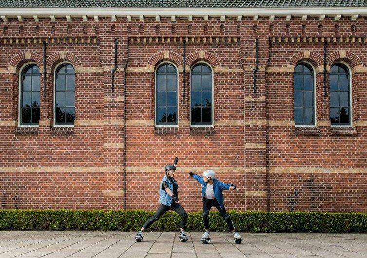 deux enfants qui jouent avec des rollers futuristes devant un mur en bric