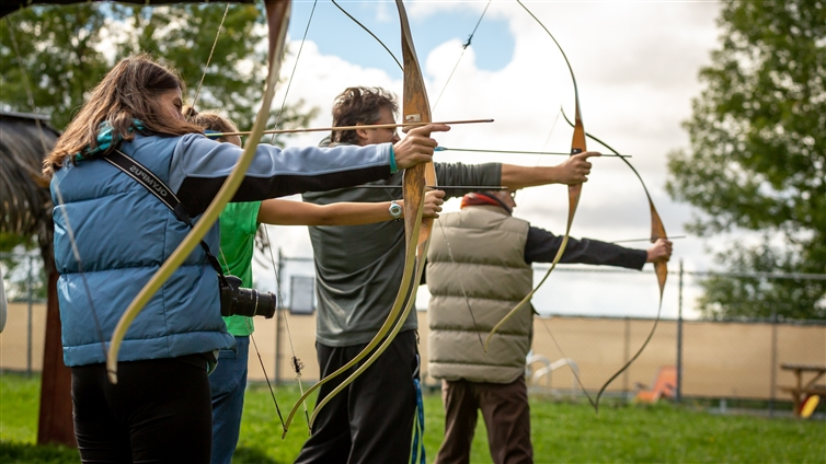 trois personnes s'exerçant au tir à l'arc