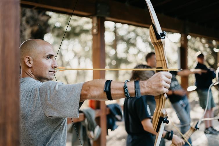 un homme en t-shirt gris tir à l'arc