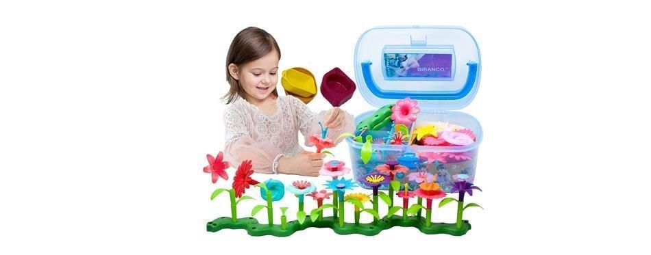 fille de 4ans joue au jardin de fleurs