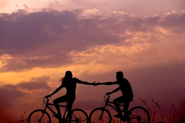 un couple amoureux à vélo qui se tient la main