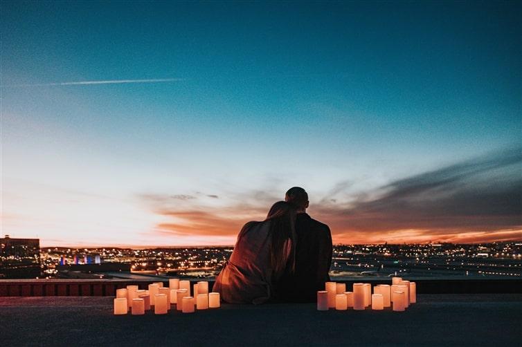 couple assis sur le terrain face à la ville