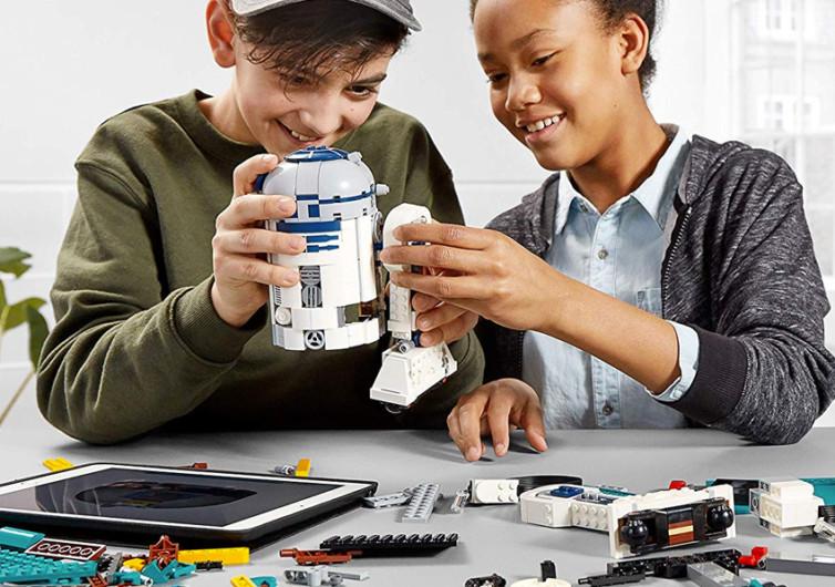 deux enfants jouent avec un robot boost lego