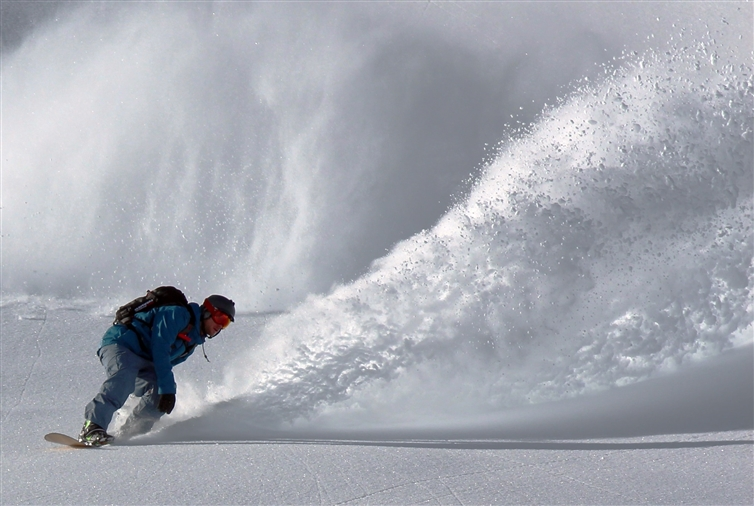 homme en snowboard qui ride une piste de ski
