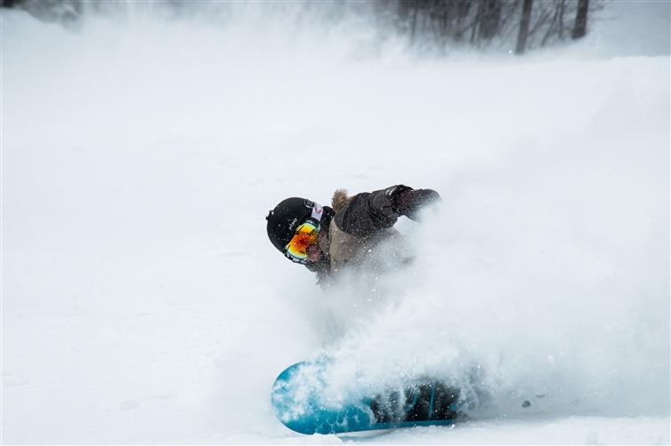 une femme qui fait du snowboard et recouvert par la neige