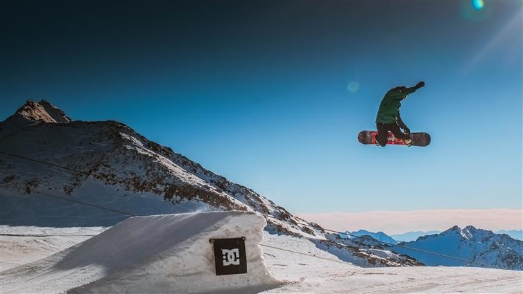 un homme en snowboard qui fait une figure en l'air