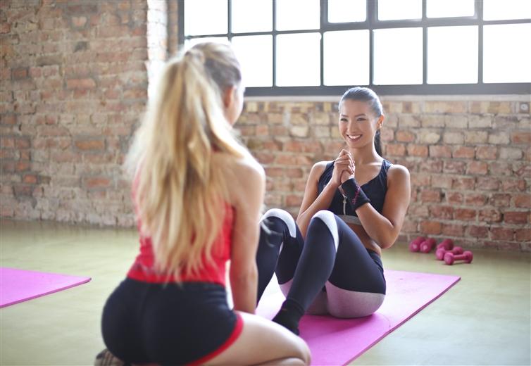 deux femmes sur un tapis de yoga qui rigole