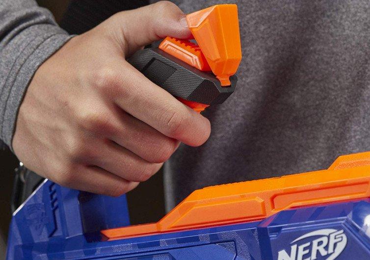 zoom sur une main qui tient un pistolet à fléches