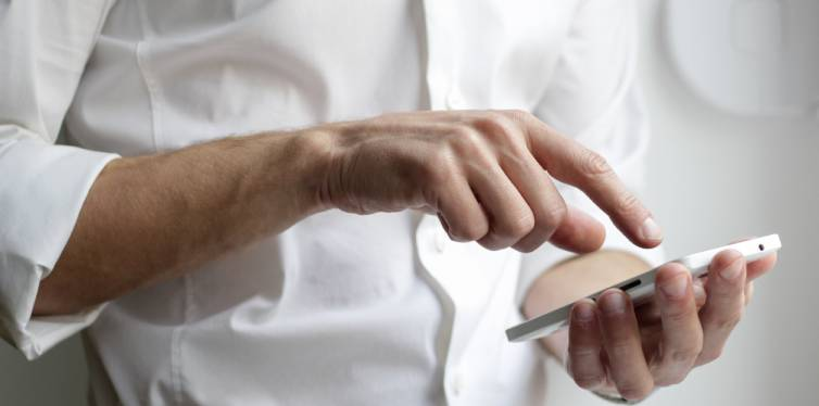 un smartphone dans les mains d'un salarié