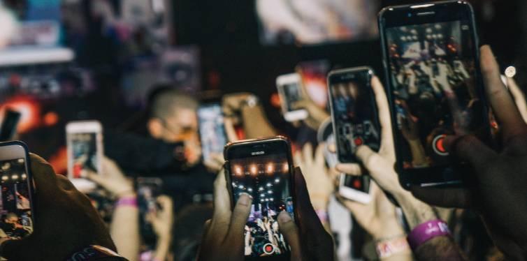 un groupe de jeune prends en vidéo une scène publique avec leurs téléphones mobiles